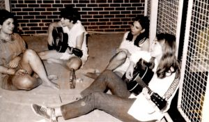 Picture of students sitting on pavement playing guitar and singing