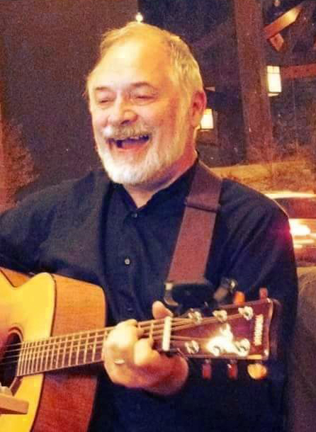 David Giddens singing and playing guitar at a coffee house