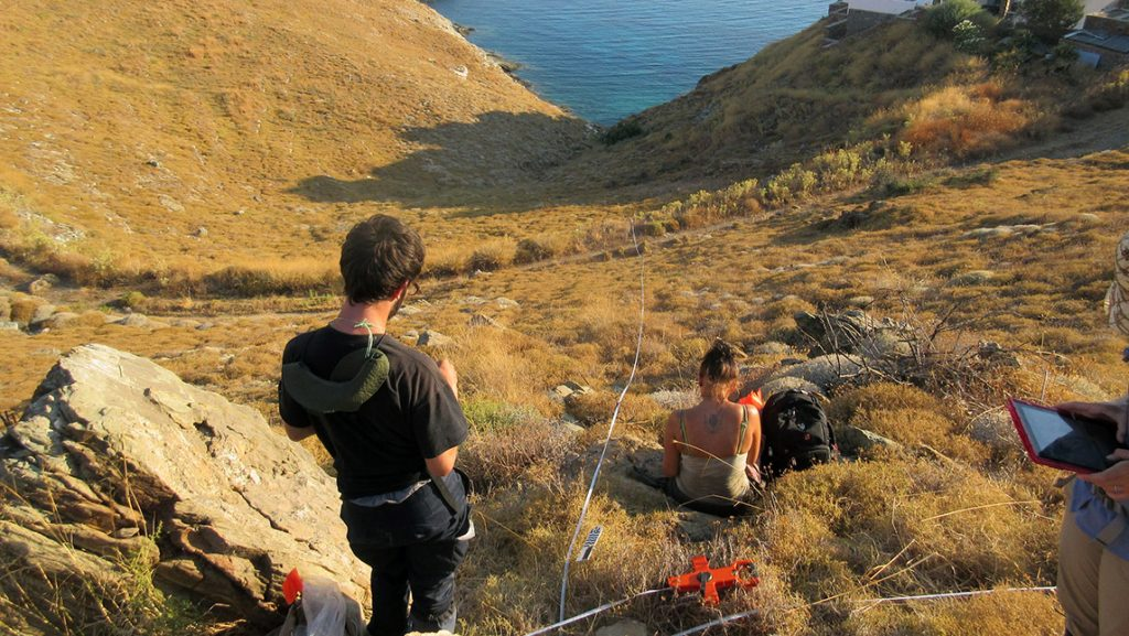Photo of two students conducting research on island