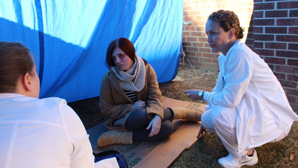 nursing students work with actors on ground