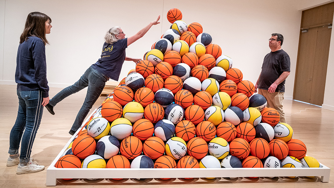 Photo of people assembling pyramid of basketballs