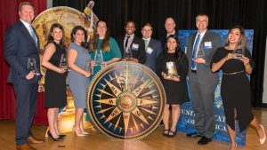 Ten UNCG alumni honorees pose for a photo with their awards
