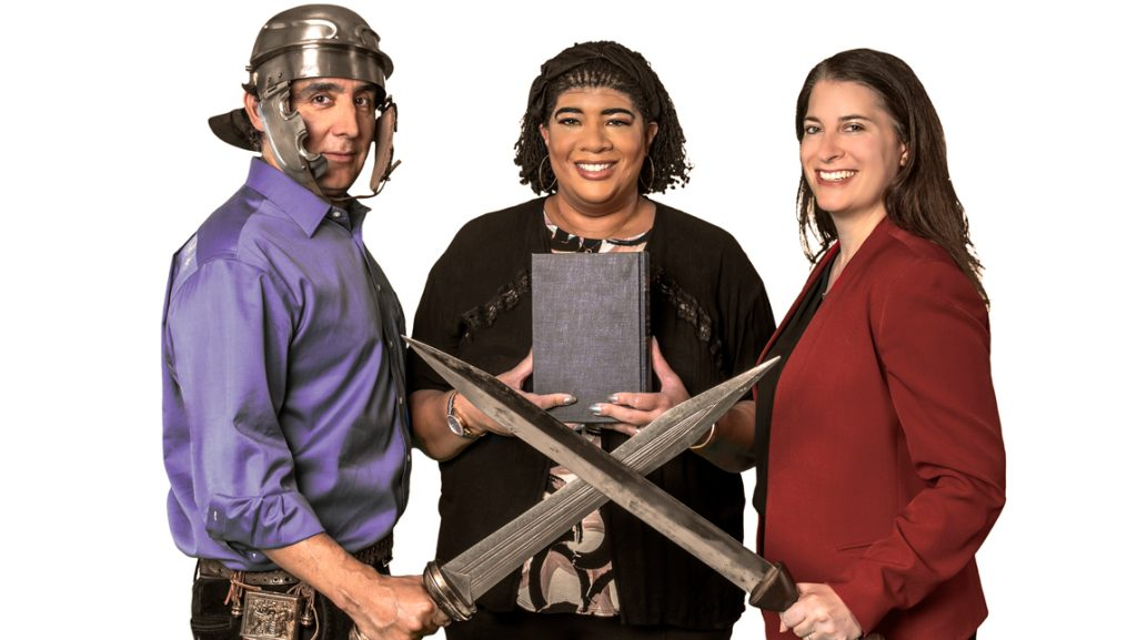 People posing with classical swords, helmets, a book.