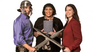people posing with classical swords, helmets, and a book