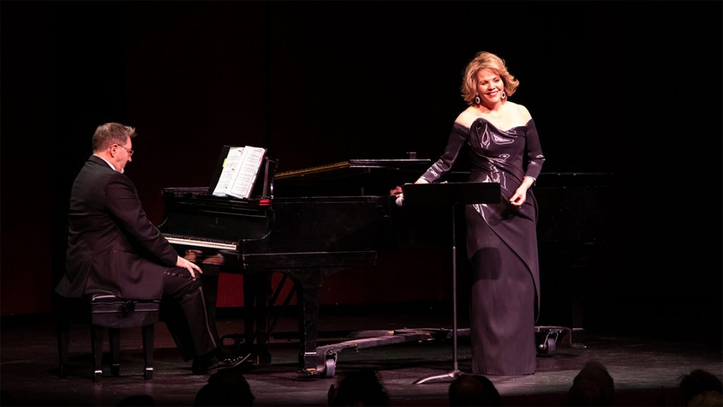 Renee Fleming smiles on stage next to piano accompaniment.
