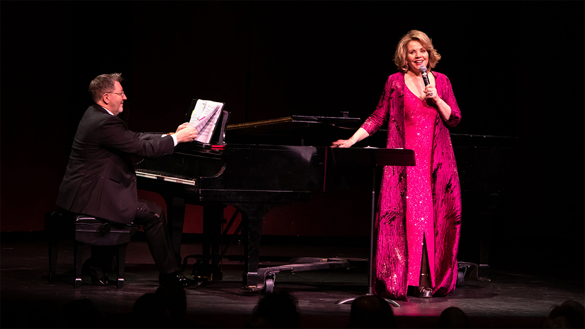 Renee Fleming singing onstage with piano accompaniment.