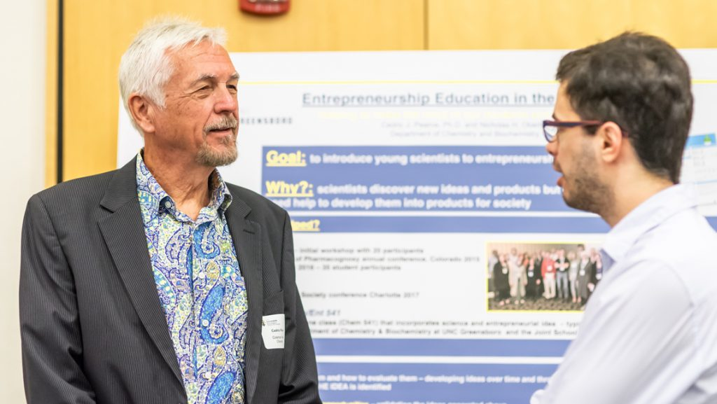 picture of researcher speaking to student in front of poster