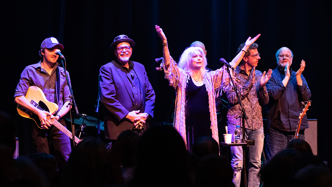 Emmylou Harris and band stand together at front of stage