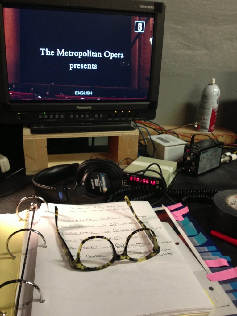 Photo of desk with notebook and glasses, among other supplies, and a TV