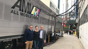 Photo of three people standing in front of large truck in city
