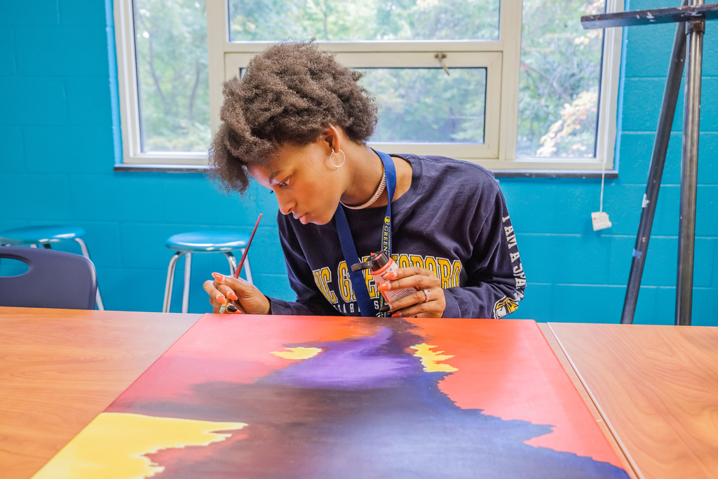 Student painting in art studio
