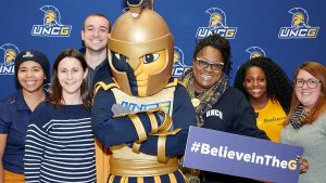 Spartans posing with Spiro mascot and #BelieveintheG sign