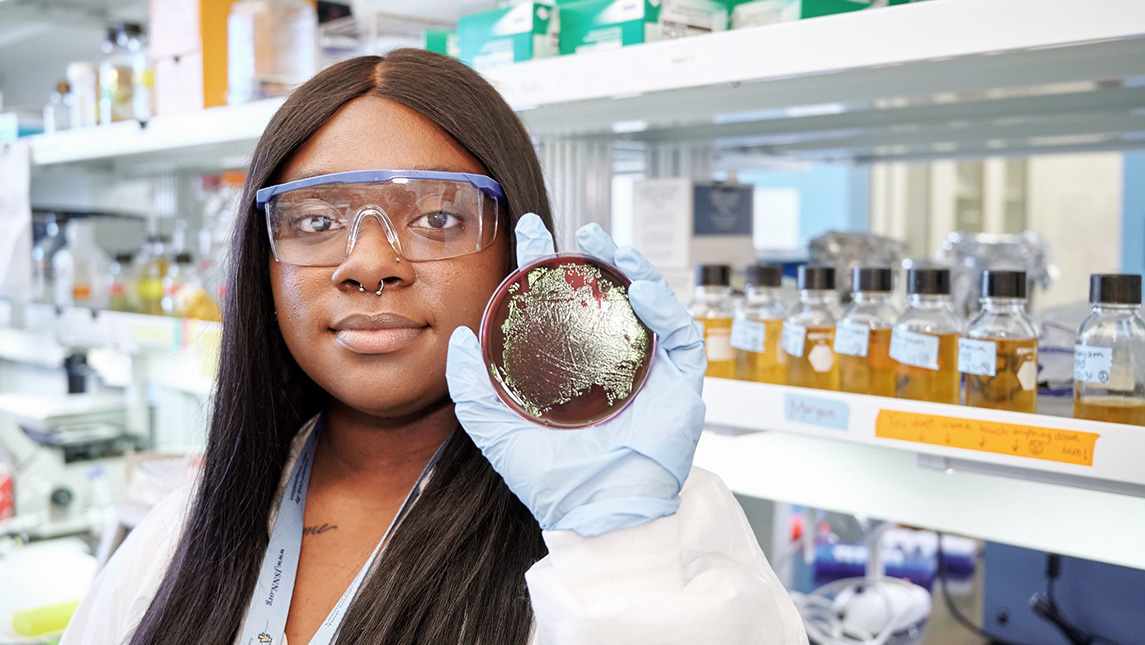 Photo of student in lab setting holding up lab dish