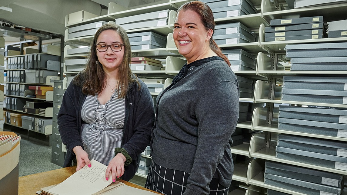 Abigail Knight with Erin Lawrimore looking at letters from President Foust from 1918