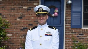Photo of Navy Ensign Quinton Smith in front of house