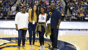 Photo of Amanda Stewart with family and coach at midcourt during game