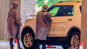 Photo of health care workers testing unidentified patient in car