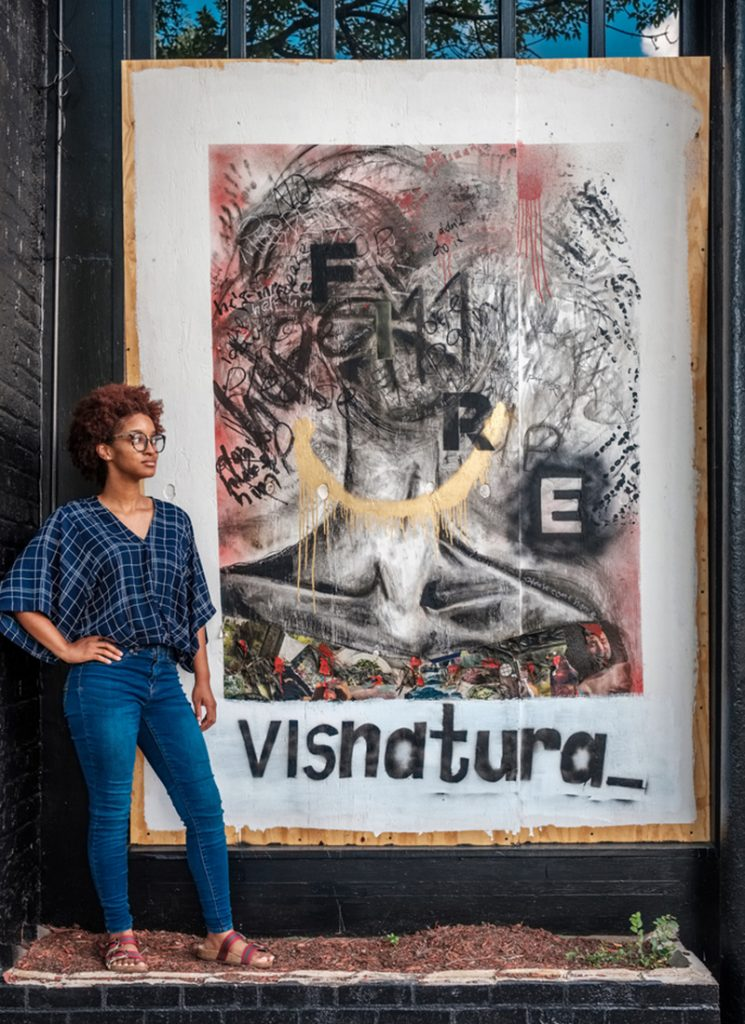 Photo of artist standing in front of painting