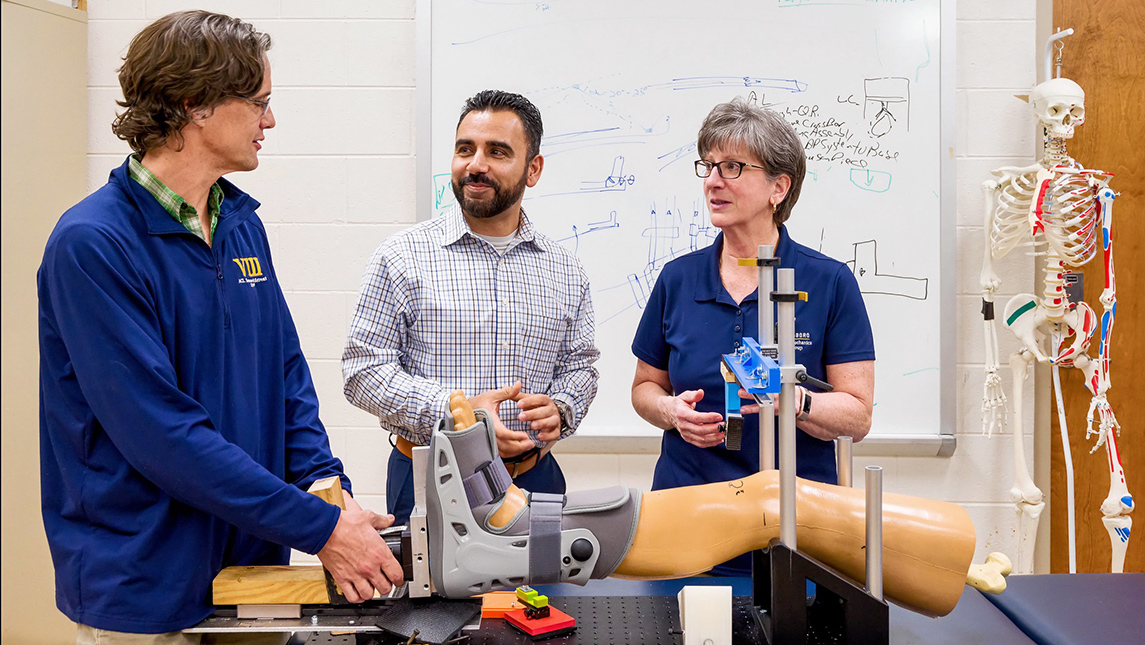 Researchers in lab setting with prosthetic leg and foot brace