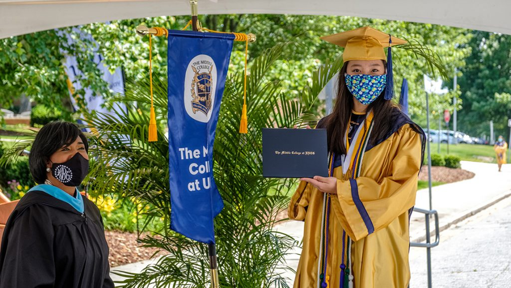 Graduate poses with diploma
