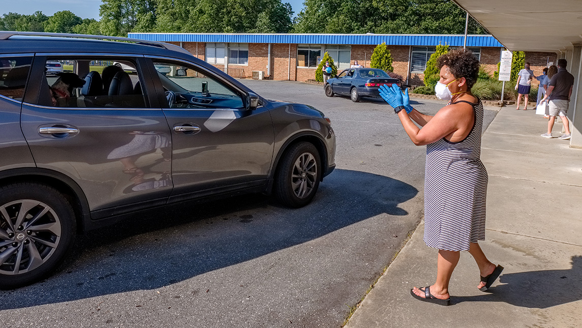 Photo of car outside of school with principal and staff on sidewalk