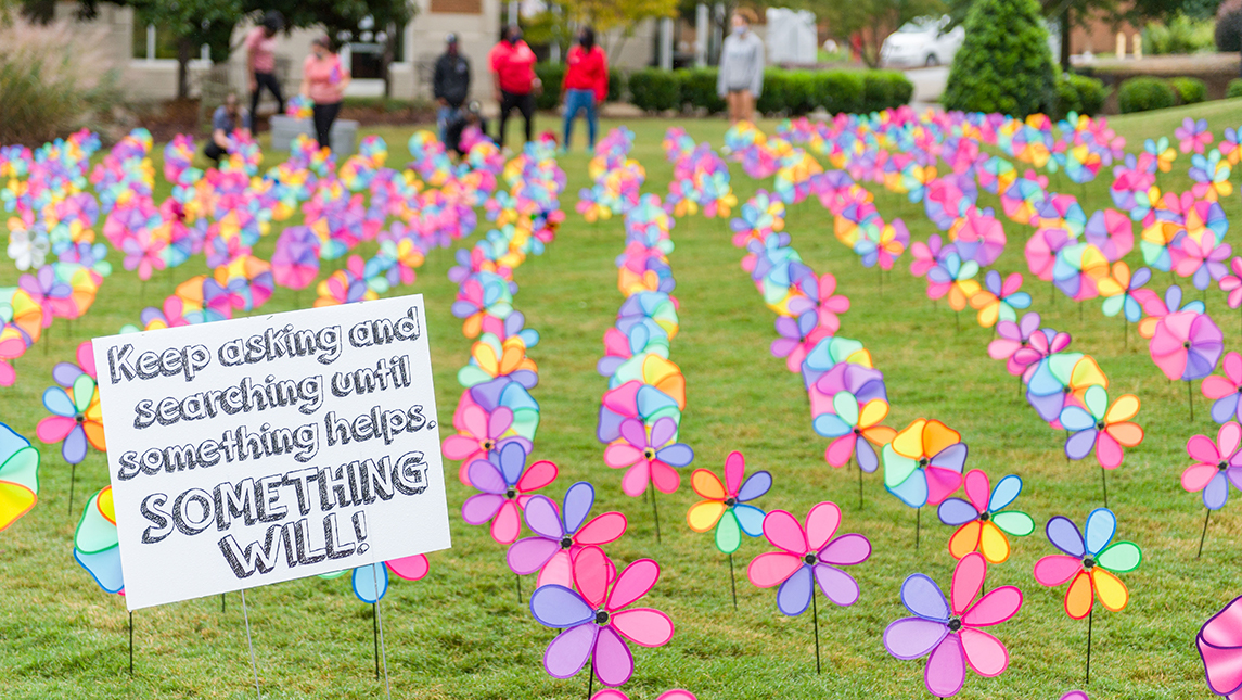 """Pinwheel display with a sign that reads: """"Keep asking and searching until something helps. Something will!"""""""