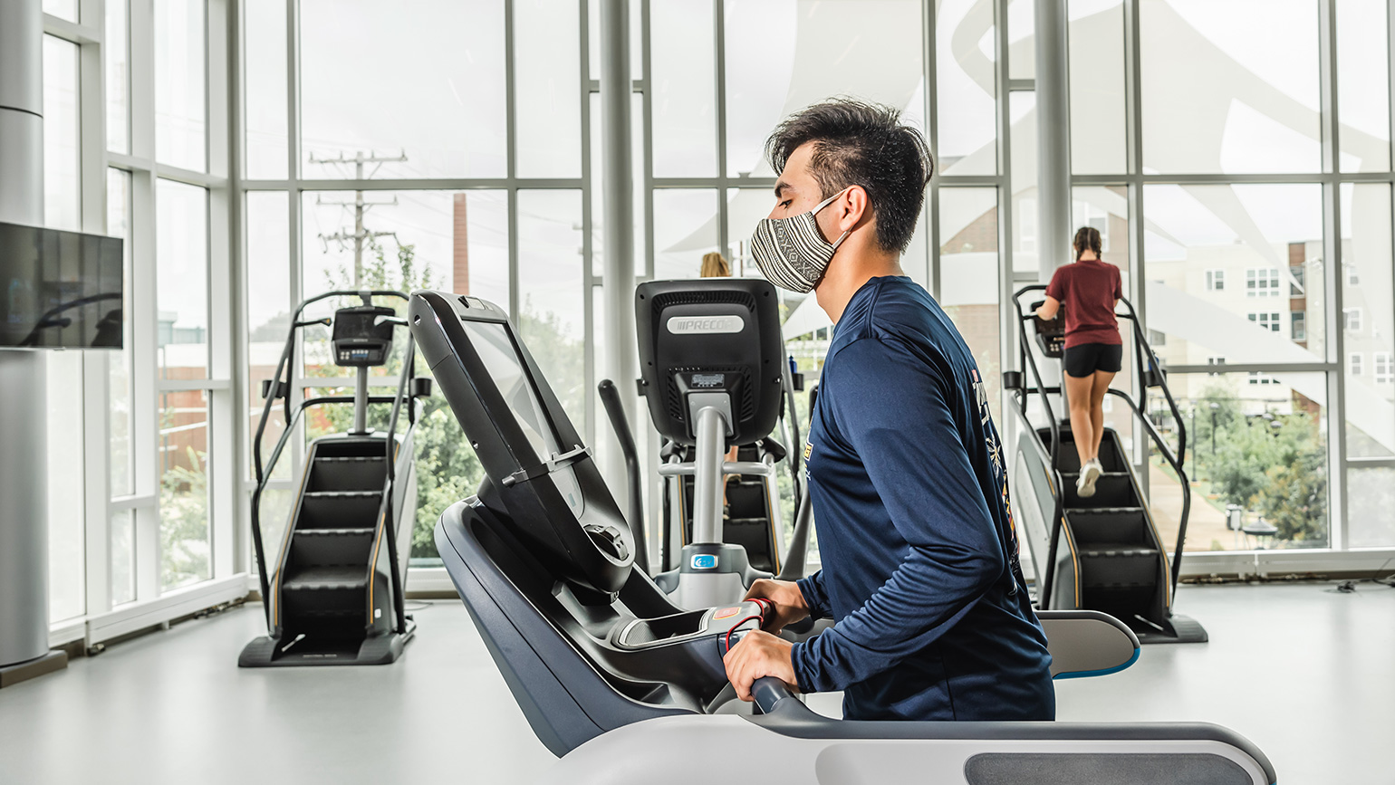 Photo of masked students using cardio equipment in gym