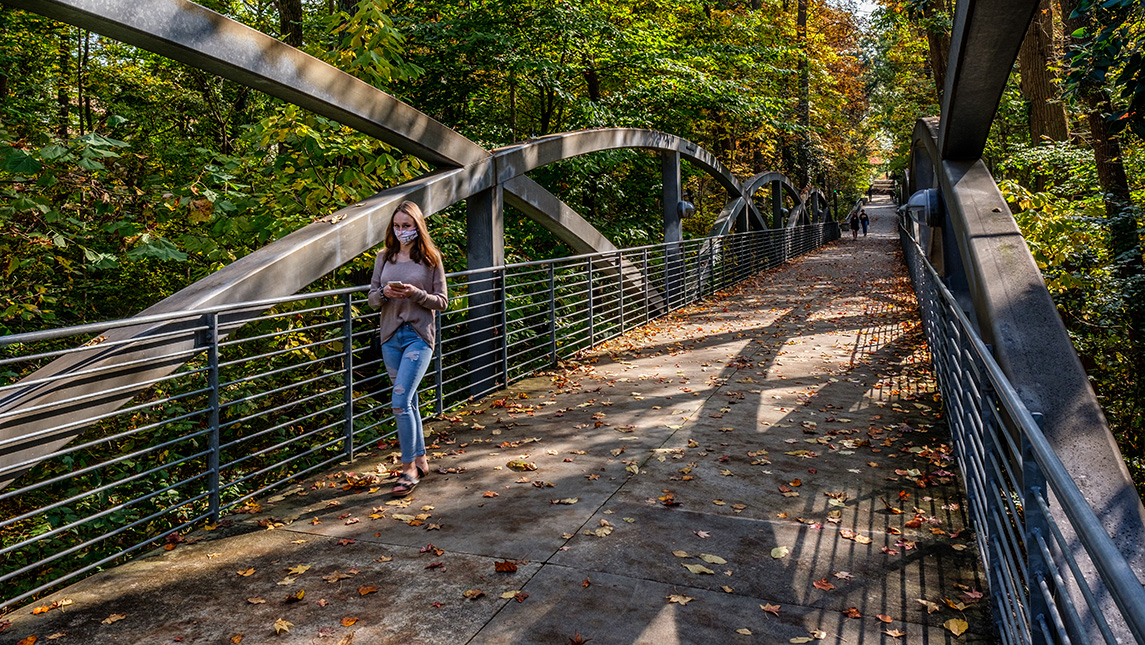 student walking on campus bridge with fall leaves