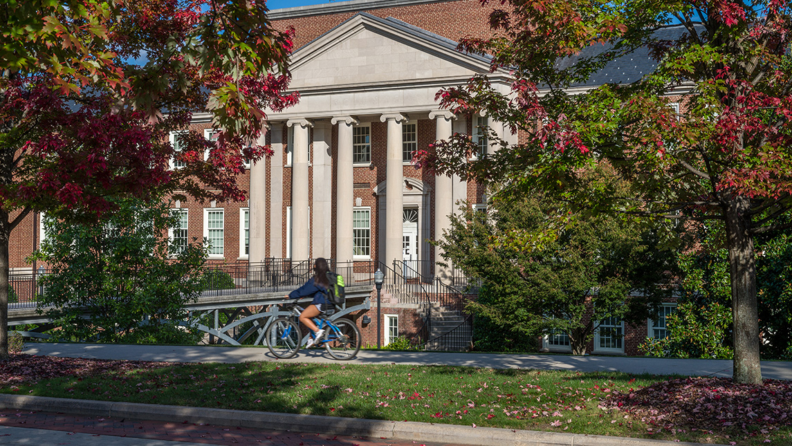 student riding bike with fall foliage and academic building