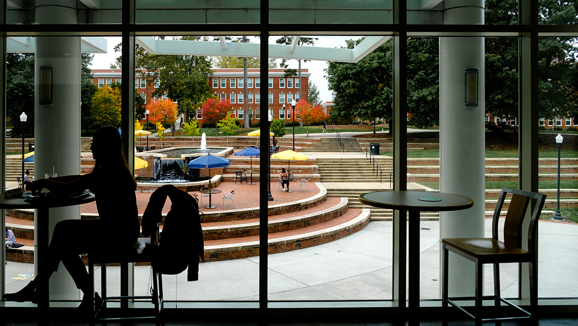 student in dining hall with fountain in background