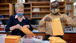 researchers opening brown envelopes