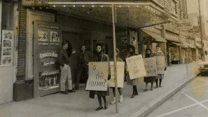archival photo of women protesting on sidewalk