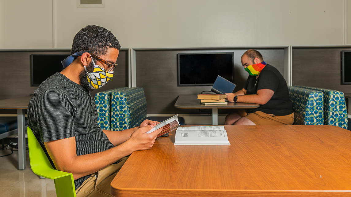 Students with face coverings studying in library