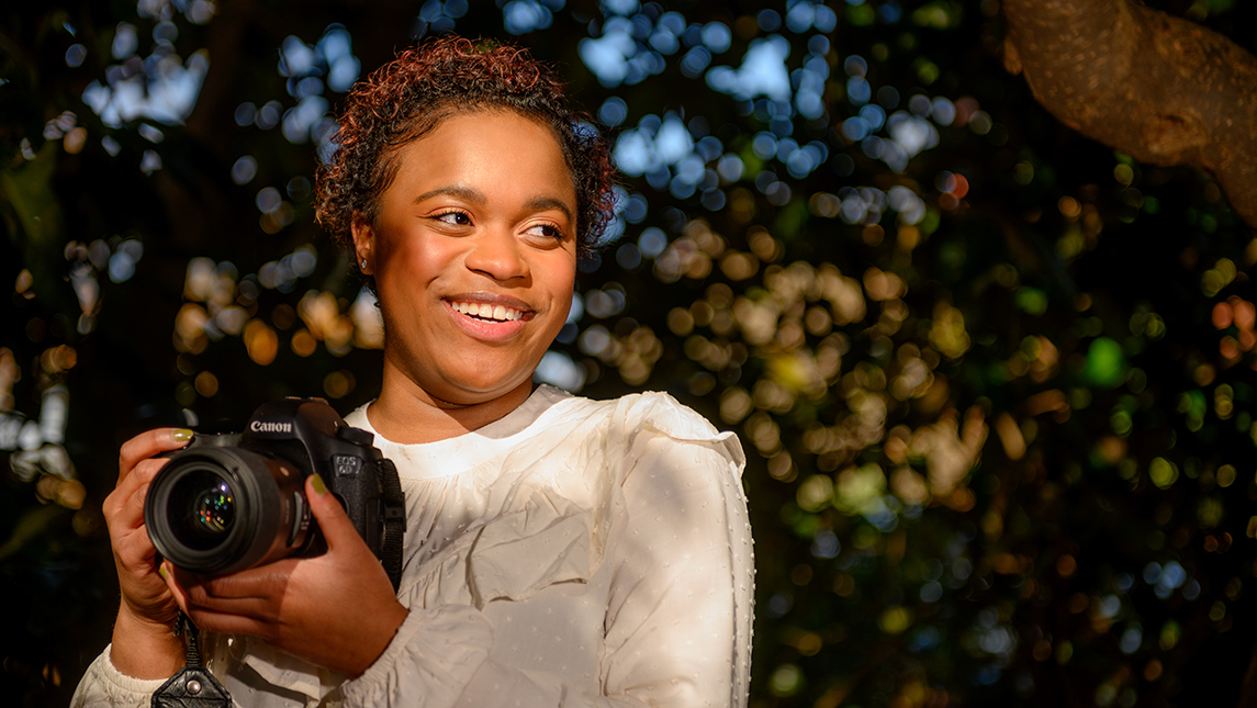 Portrait of Alycee Byrd with camera on campus
