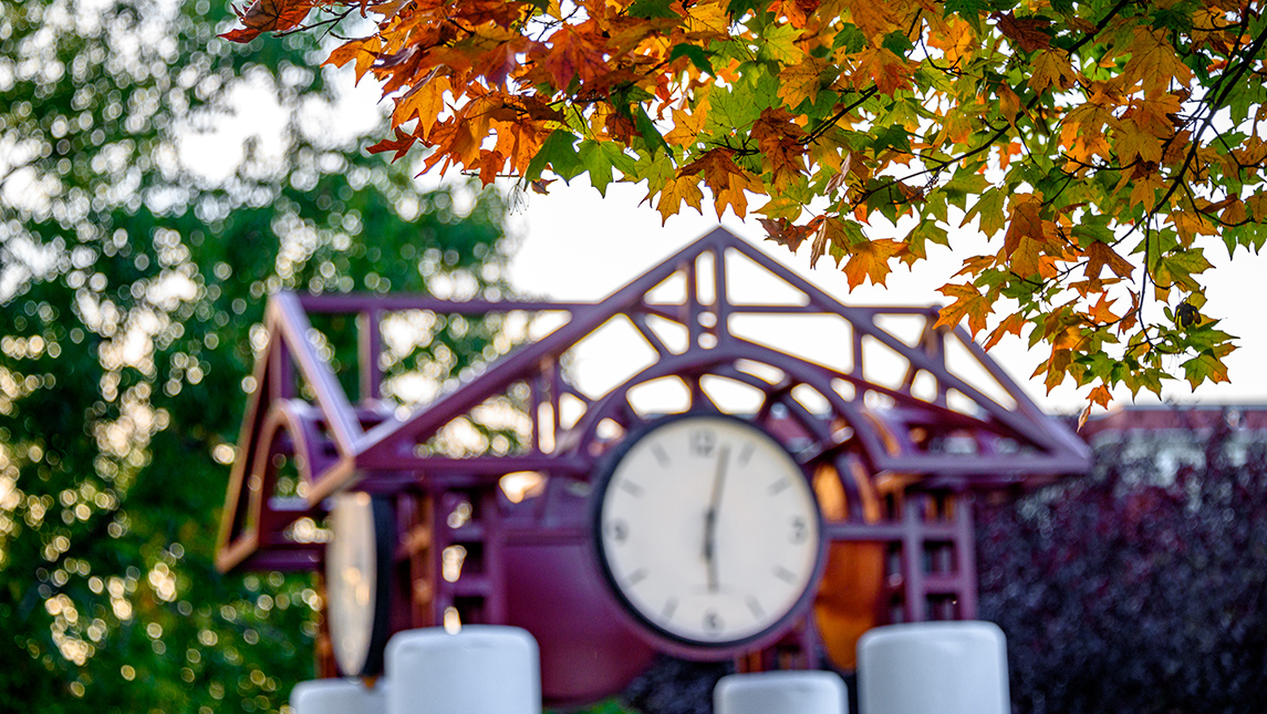 Photo of clock tower with fall foliage