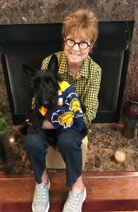 Photo of Dean Remsburg and her dog in front of fireplace