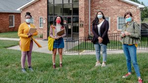 Photo of four community health workers standing outside with masks