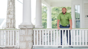 Photo of Dr. Torren Gatson standing on front porch of Magnolia House