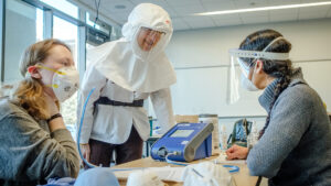 Two women help student get fitted for N95 mask