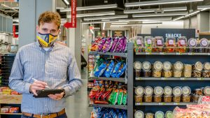 Photo of professor holding tablet in grocery store