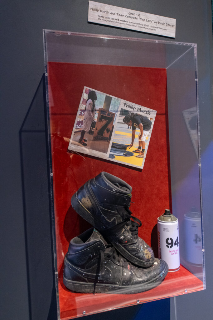 """The shoes Marsh wore and the spray paint he used during the painting of the """"One Love"""" street installation on display in the exhibit"""