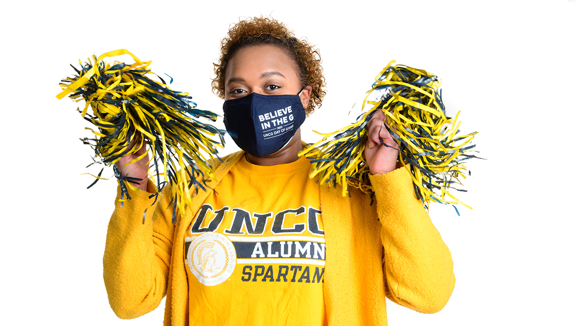 Photo of alumna in UNCG gear with UNCG pom poms