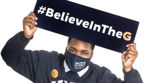 Image of man with UNCG gear holding up Believe in the G sign