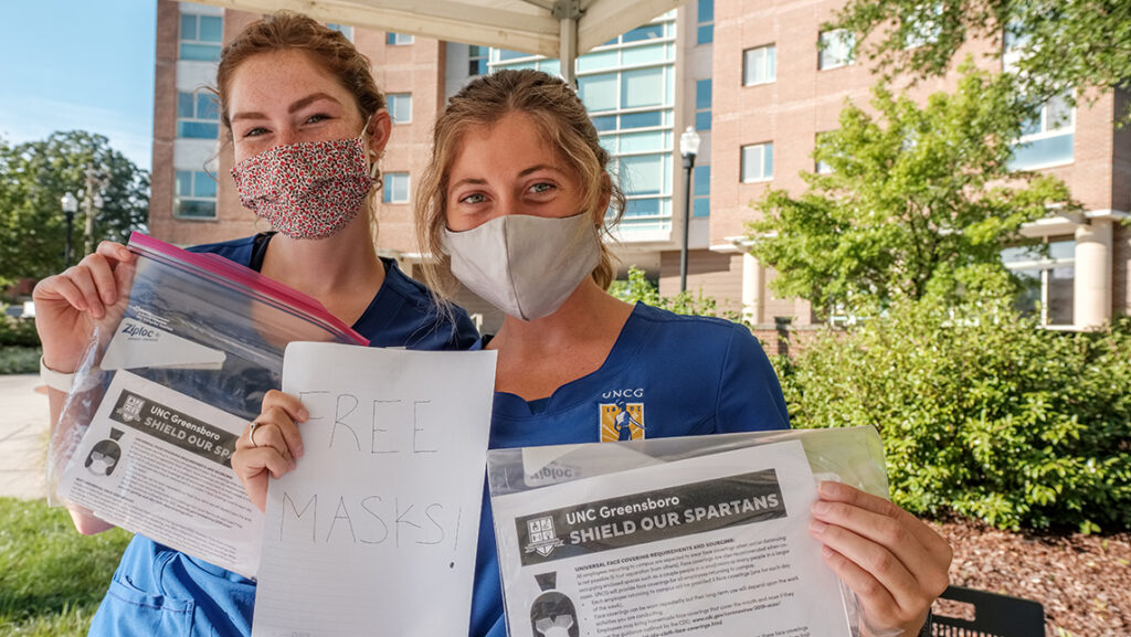Two nursing students wearing face coverings pose with bags of free masks to be given out to campus community
