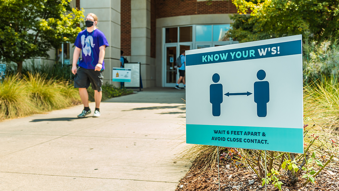 """Sign on campus that reads """"KNOW YOUR W'S! WAIT 6 FETT APART AND AVOID CLOSE CONTACT"""""""