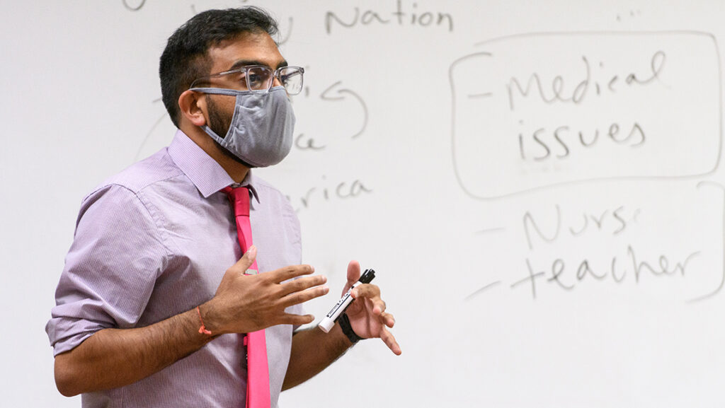 Professor wearing face covering teaches in front of a white board