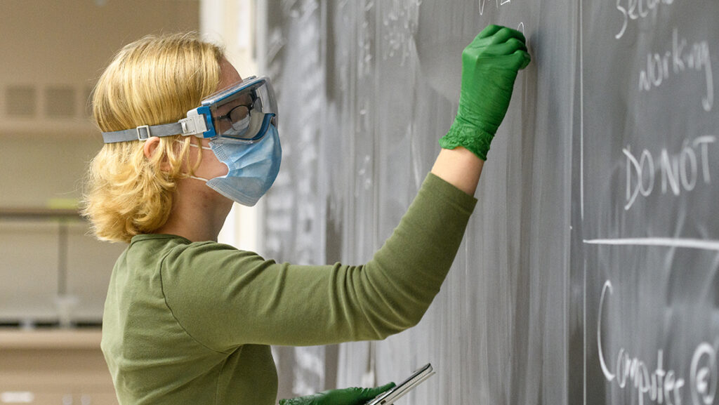 Woman in goggles, mask, and gloves writes on a chalkboard