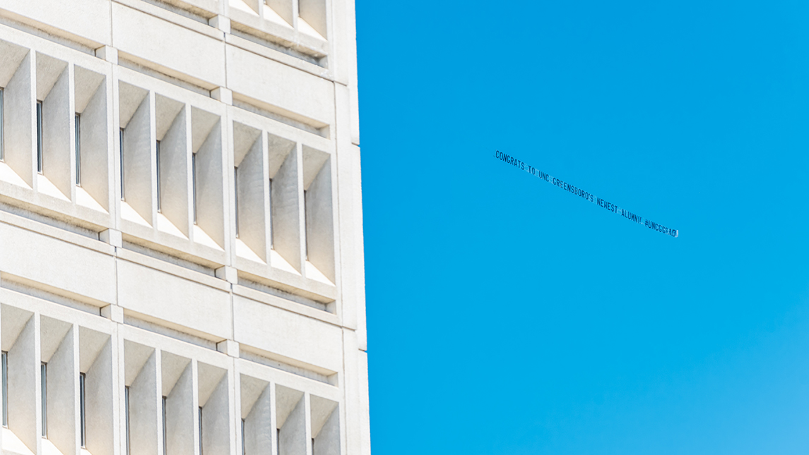 """Airplane flying a banner in the sky reading """"CONGRATS TO UNC GREENSBORO'S NEWEST ALUMNI #UNCGGRAD"""""""