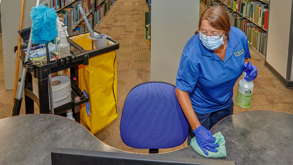 Housekeeper sanitizes a surface in the library