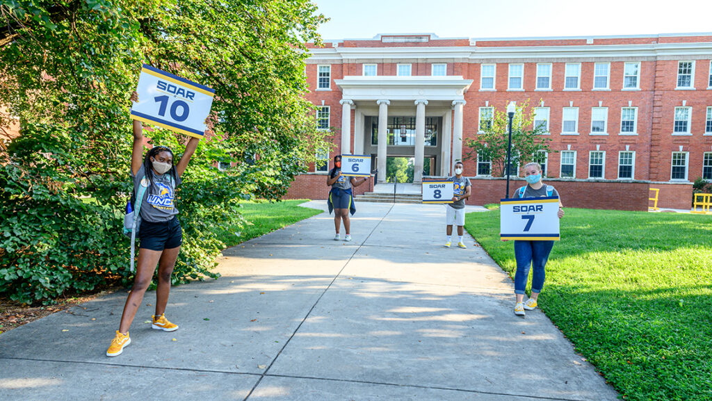 Student SOAR leaders standing six feet apart holding numbered signs